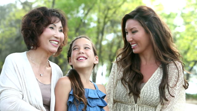 Girl, mother and grandmother laughing together at park