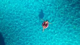 Girl on a circle swimming in the pool