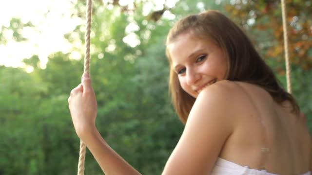 girl on a rope swing smiling at the camera - vackra människor bildbanksvideor och videomaterial från bakom kulisserna