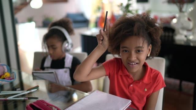 vídeos de stock, filmes e b-roll de garota em uma aula virtual, levantada à mão - de braço levantado