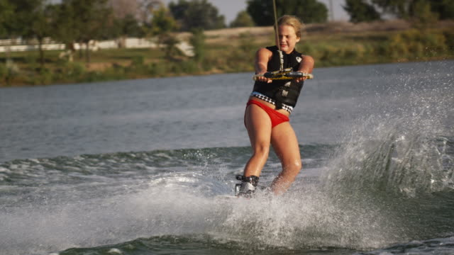 girl on a wakeboard behind a boat - wakeboarding stock videos and b-roll footage