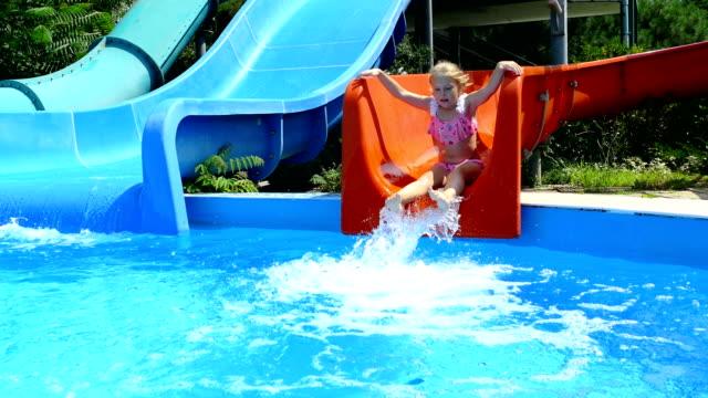 flicka på en vattenrutschbana i hotellets pool - utebassäng bildbanksvideor och videomaterial från bakom kulisserna
