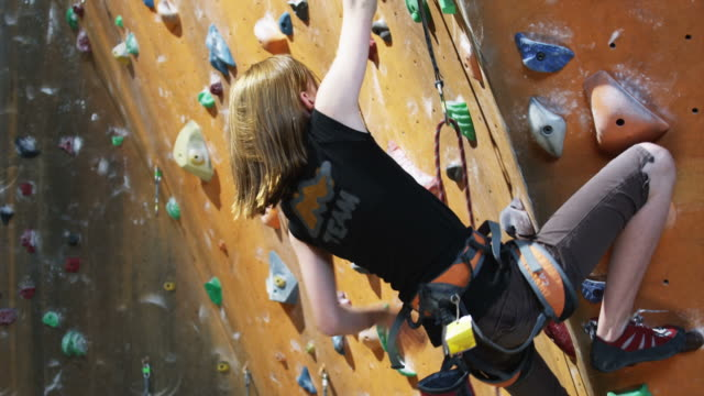 girl on an indoor climbing wall - kletterwand kletterausrüstung stock-videos und b-roll-filmmaterial