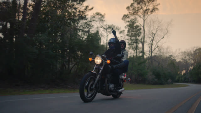 SLO MO. Girl on back of motorcycle points ahead and motorcycle driver points up at the sky on road trip adventure.