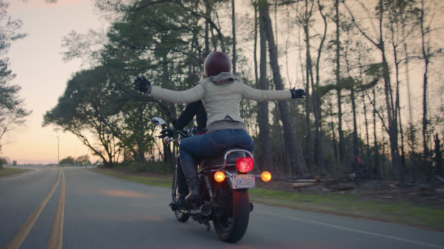 SLO MO. Girl on back of motorcycle waves arms in the air and hugs driver tight on sunset road trip.