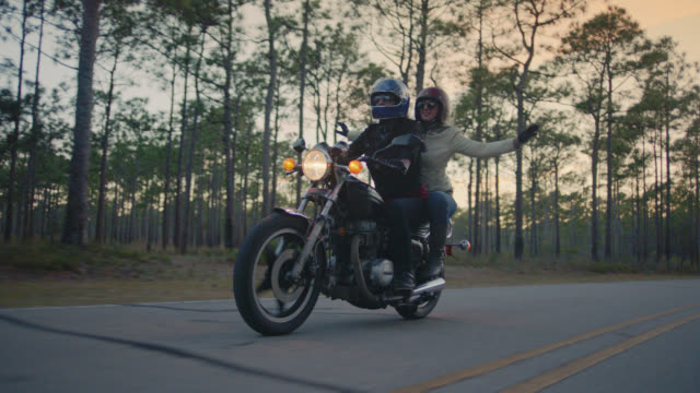 SLO MO. Girl on back of motorcycle waves arms in the air as boyfriend drives down forest highway on road trip.