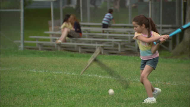 SELECTIVE FOCUS MS Girl on baseball field attempting to hit baseball off of tee and missing/ Girl picking up ball as man walks in and picks up the tee/ Fanwood, New Jersey