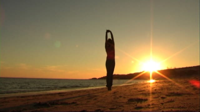 girl on beach doing acrobatics - londonalight stock videos and b-roll footage
