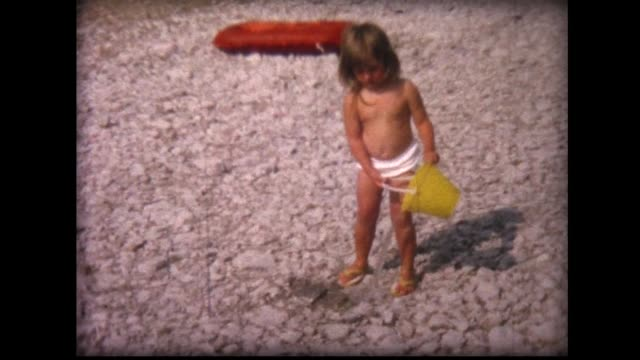 1964 girl on beach pours water from yellow bucket