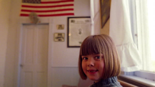 ms portrait girl on bench in schoolhouse smiles to reveal missing teeth / american flag in background - 分校点の映像素材/bロール