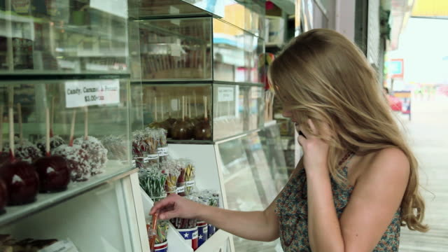 girl on cellphone by confectionery shop - fairground stall stock videos & royalty-free footage