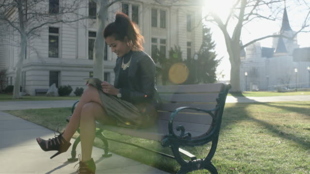 girl on city park bench with tablet - footwear stock videos & royalty-free footage