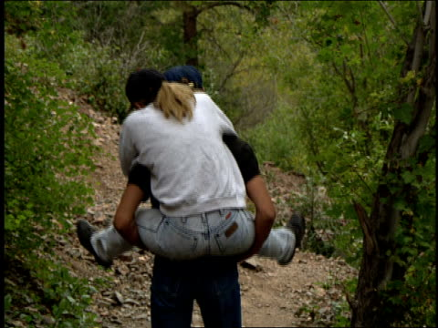 girl on guy's back walking through the wyoming woods - portare a cavalluccio video stock e b–roll