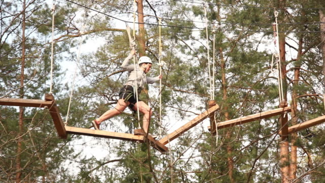 Menina com fios de cabos naturalmente, com árvores (Desportos de aventura