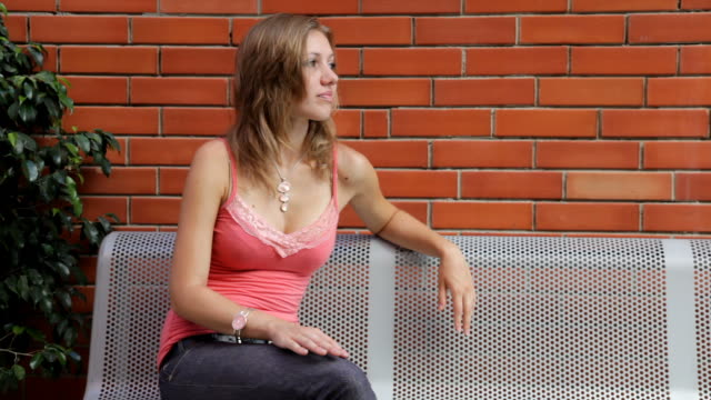 girl on metal bench - red brick background - girl sitting cross legged stock videos & royalty-free footage