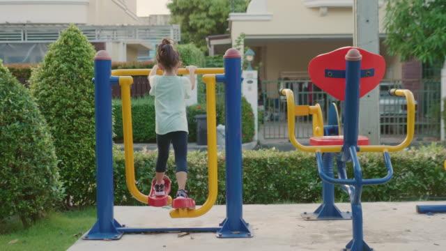 vídeos y material grabado en eventos de stock de una chica en el equipo del patio. - estructura metálica para niños