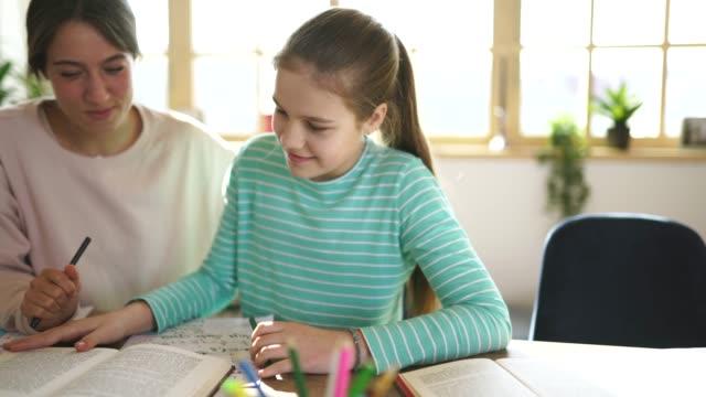 vidéos et rushes de fille sur la classe privée avec le professeur de jeune femme à la maison - cours de mathématiques