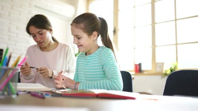 vídeos de stock, filmes e b-roll de menina na classe confidencial com professor da mulher nova - sentando