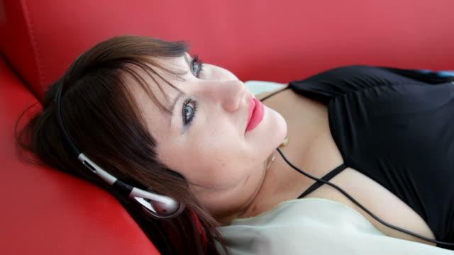 Girl on red sofa enjoys the music in headphones