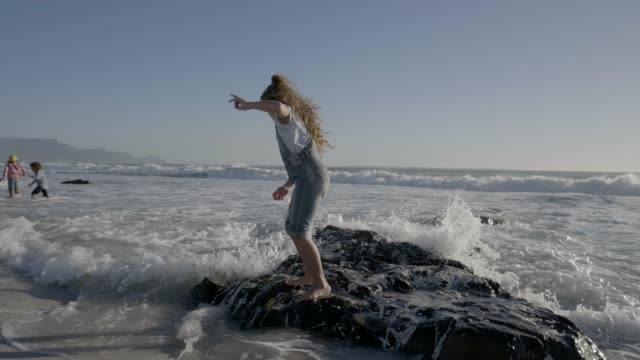 girl on rock formation running from waves at beach - beach holiday stock-videos und b-roll-filmmaterial