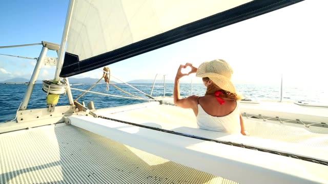 Mädchen auf Segelboot macht Herzen Formrahmen finger
