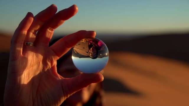 girl on sand desert reflecting in a glass ball - looking through an object stock videos and b-roll footage