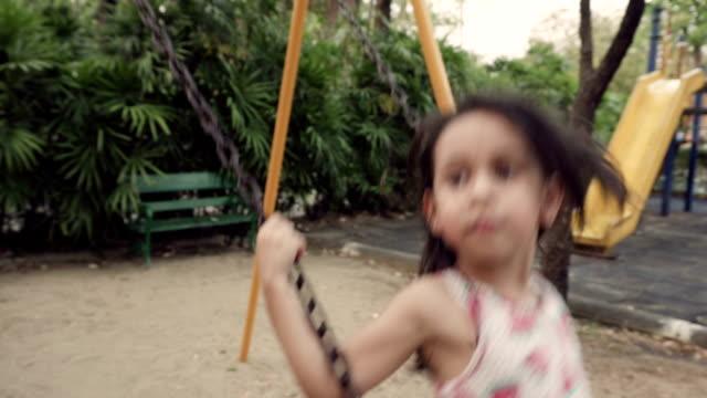 vídeos y material grabado en eventos de stock de niña en columpio en el parque público - columpiarse