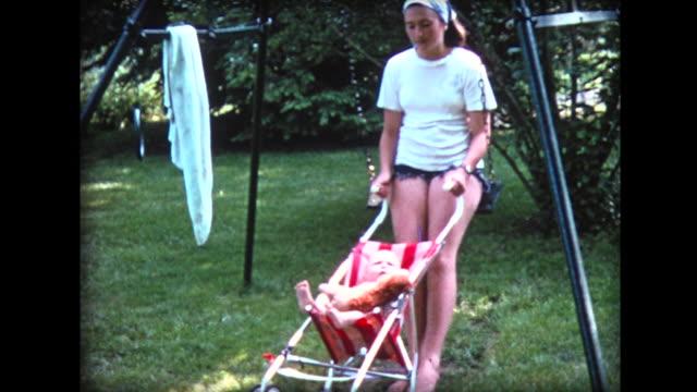 vidéos et rushes de 1974 girl on swing rocking baby in stroller - nurse
