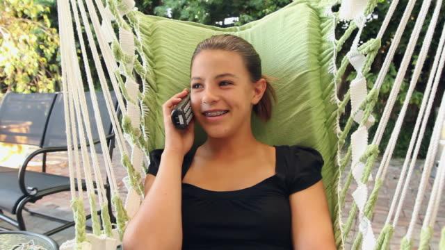 stockvideo's en b-roll-footage met ms girl (12-13) on swing, talking on telephone / buffalo, new york, usa - draadloze telefoon