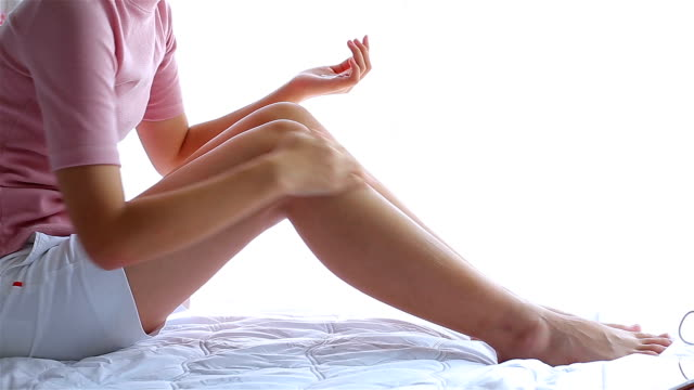 Girl on the bed to put a cream on legs. beautiful woman skin care