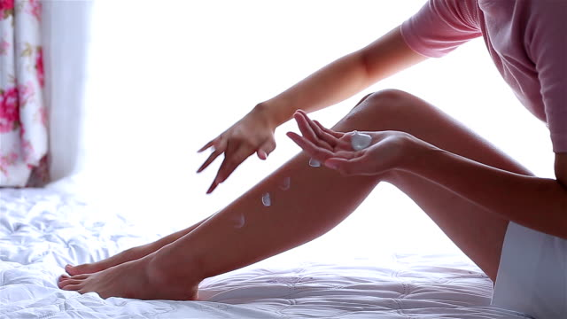 girl on the bed to put a cream on legs. beautiful woman skin care - prendersi cura del corpo video stock e b–roll