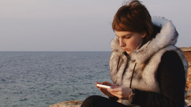 Girl on the coast with phone