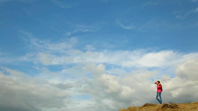 mädchen auf berggipfel gegen den himmel - rucksack stock-videos und b-roll-filmmaterial