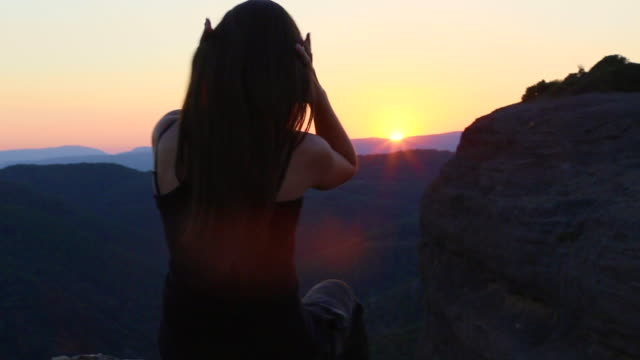 girl on top of the mountain contemplating the sunset over the catalan pyrenees mountains touching his long hair in a quiet and relax place. - maglietta senza maniche video stock e b–roll