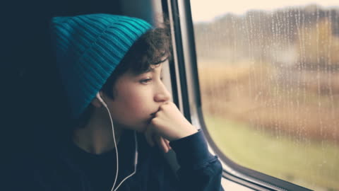 girl on train looking through window - hörlurar bildbanksvideor och videomaterial från bakom kulisserna