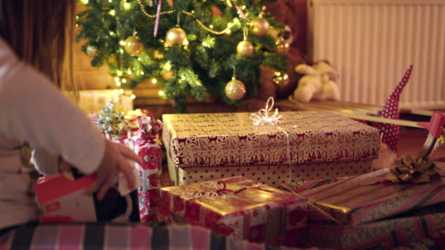 4k girl opening christmas gifts near christmas tree, real time - christmas gift stock videos and b-roll footage