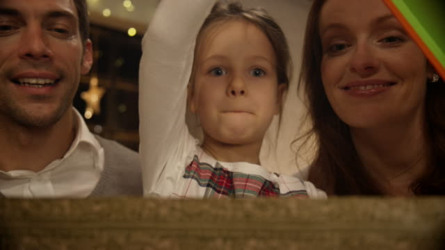 girl opening christmas present with parents - income tax stock videos and b-roll footage