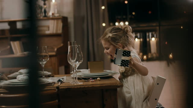 girl opening present on dinner table - atmospheric mood stock videos & royalty-free footage