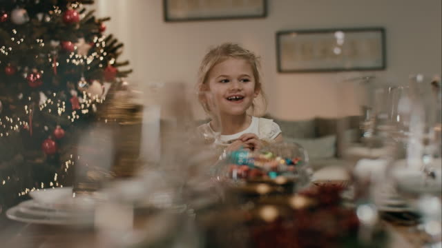 Girl opening present on dinner table