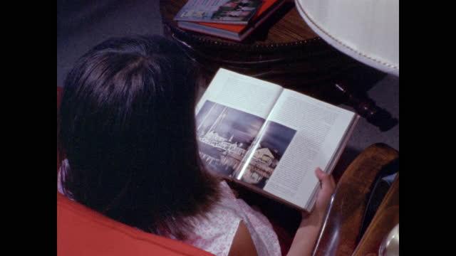 vidéos et rushes de girl opens book with shiny pages on lap - petites filles