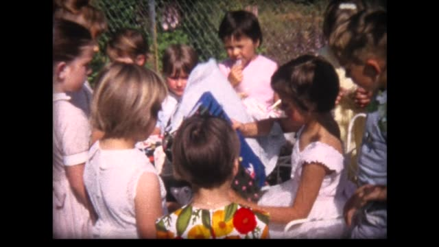 1964 girl opens presents surrounded by friends - kind im grundschulalter stock-videos und b-roll-filmmaterial