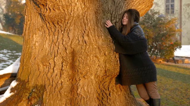 Girl outdoors enjoying bonding with nature hugging a big tree