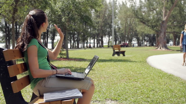 ms pan girl (14-15) outdoors typing on laptop and meeting fellow students / cape coral, florida, usa - waving hello stock videos & royalty-free footage