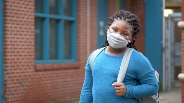 girl outside elementary school wearing face mask - elementary school building stock videos & royalty-free footage