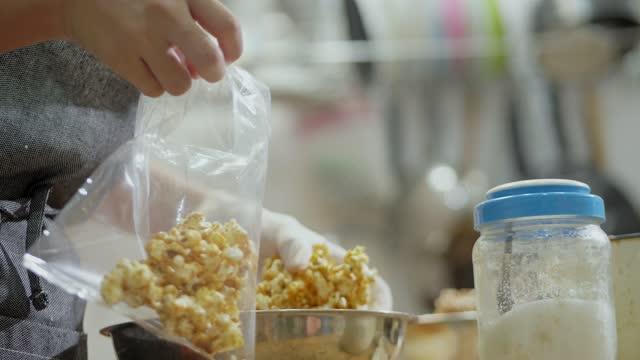 vídeos de stock, filmes e b-roll de garota embalando pipoca em saco plástico para vender, pequeno negócio em casa conceito. garota aprendendo para ganhar dinheiro para si mesma no fim de semana. - fazer
