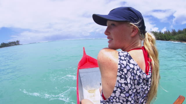 vidéos et rushes de girl paddling at nose of an outrigger looks back at camera smiling - turtle bay oahu