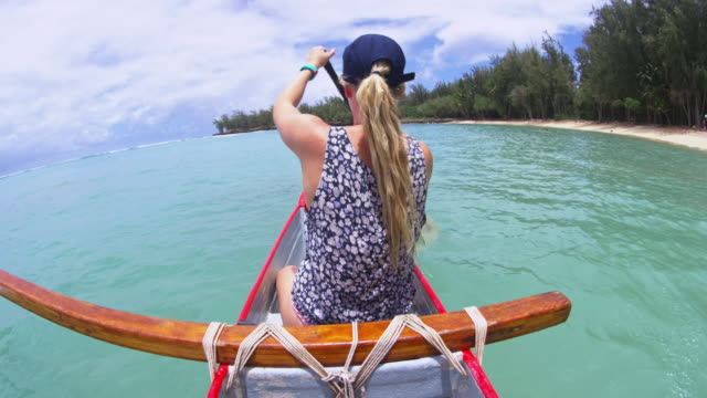 vidéos et rushes de a girl paddling at nose of an outrigger - turtle bay oahu