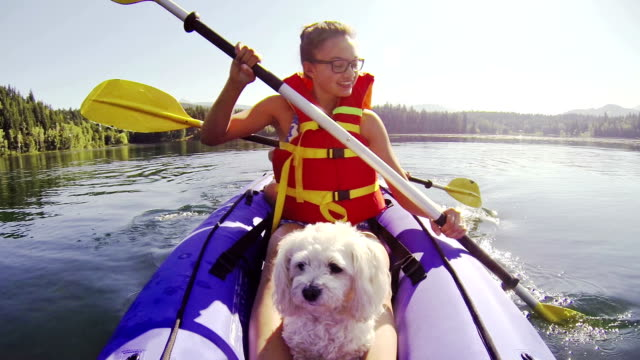 Girl paddling Kayak across a lake with pet dog