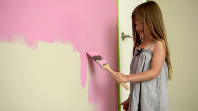 Girl painting her bedroom pink