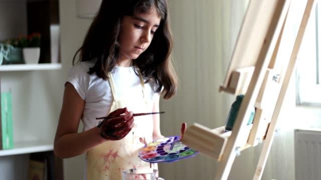 イーゼルの絵画の女の子 - 絵筆点の映像素材/bロール